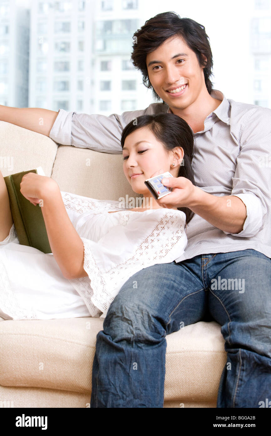 Asian Couple Cuddling On A Sofa   Stock Image