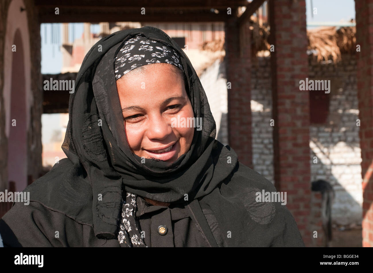 Young Egyptian woman with robe and scarf in a village market along the Nile River Valley - Stock Image