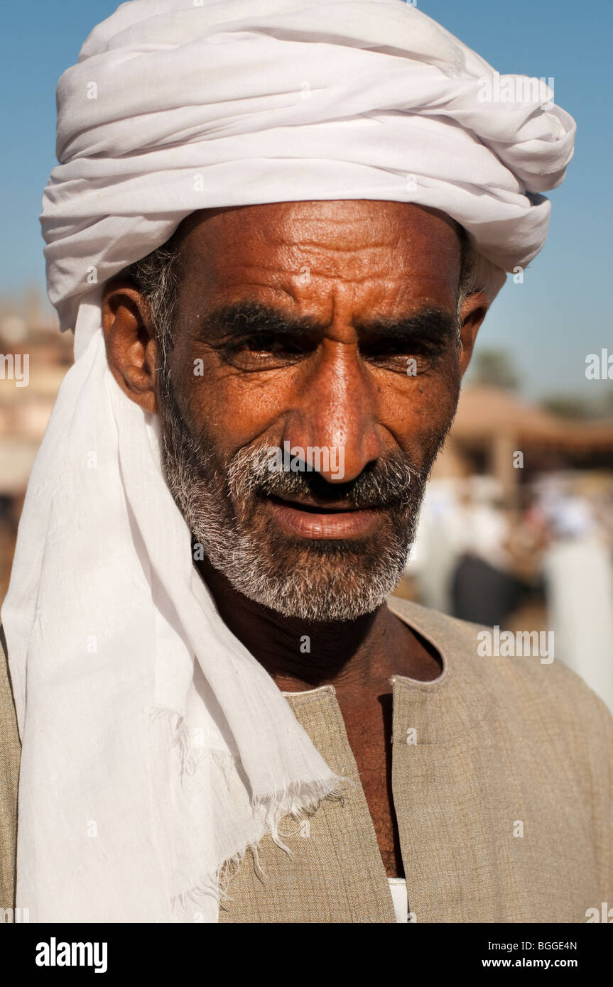 Portrait of an Egyptian man in a turban while selling camels in a market along the Nile - Stock Image