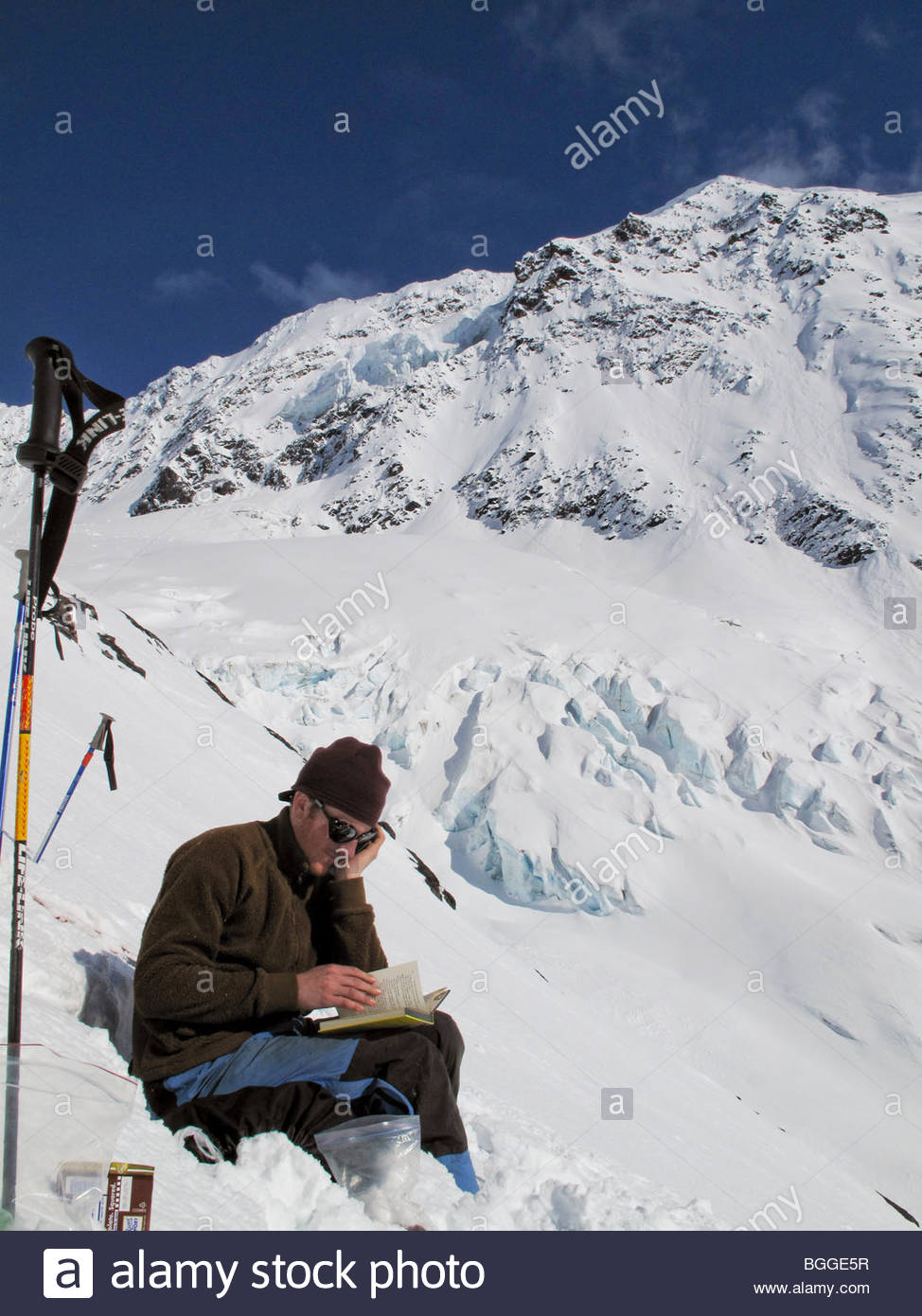 A backcountry skier pauses for a bit of reading, Chugach Mountains, Alaska. - Stock Image