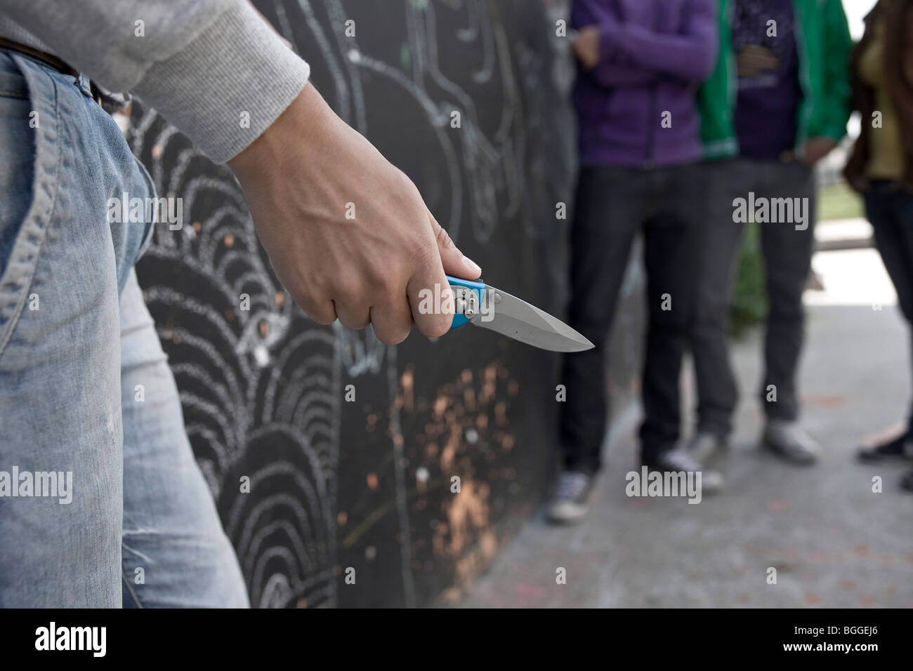 Young man holding a pocketknife, teenager in the background - Stock Image