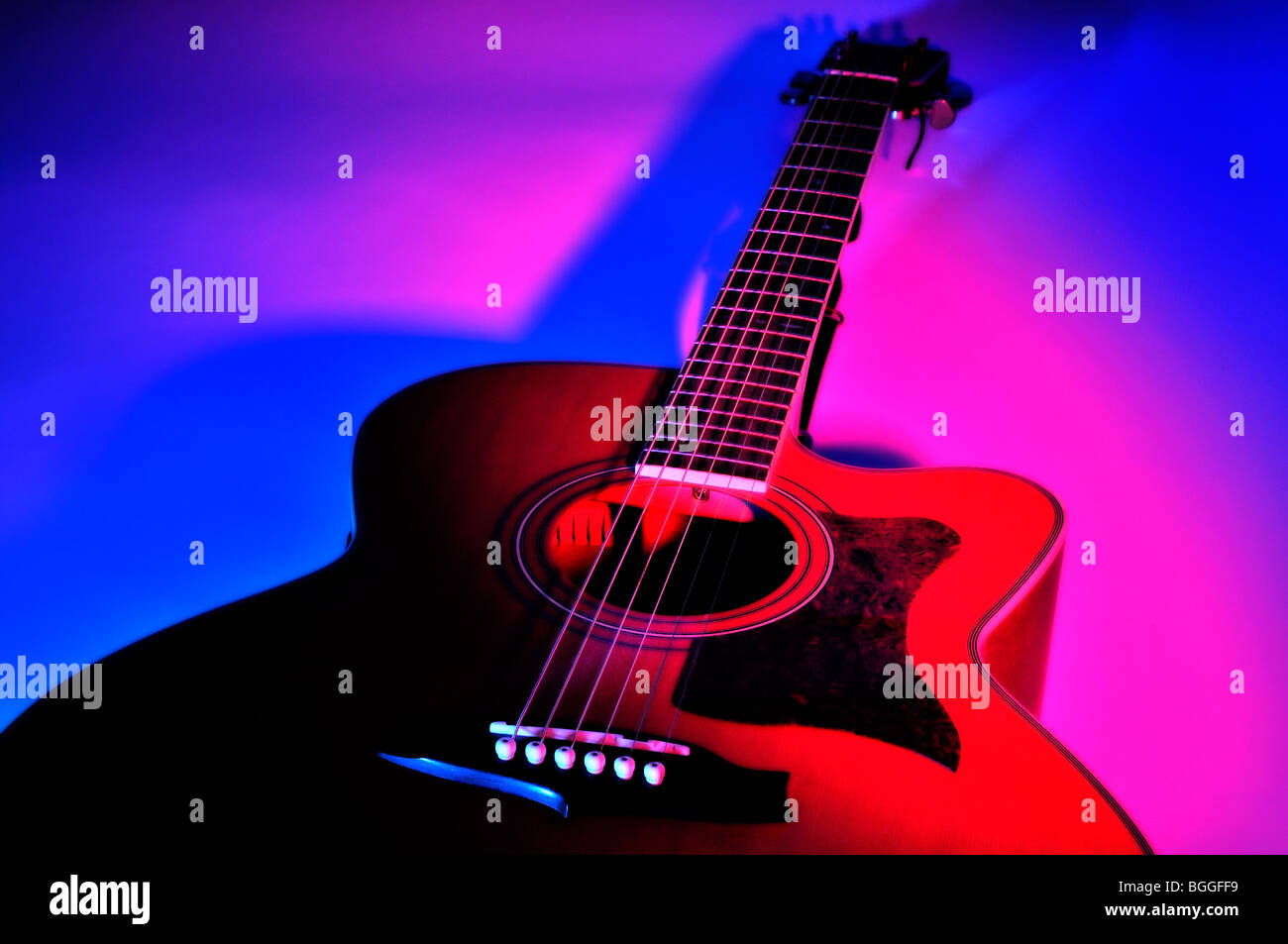 Studio shot six string acoustic guitar under coloured lights Stock