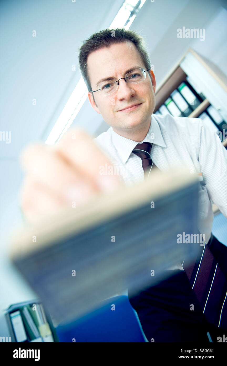 Man holding a stamp towards camera, facing camera, low angle view, close-up - Stock Image