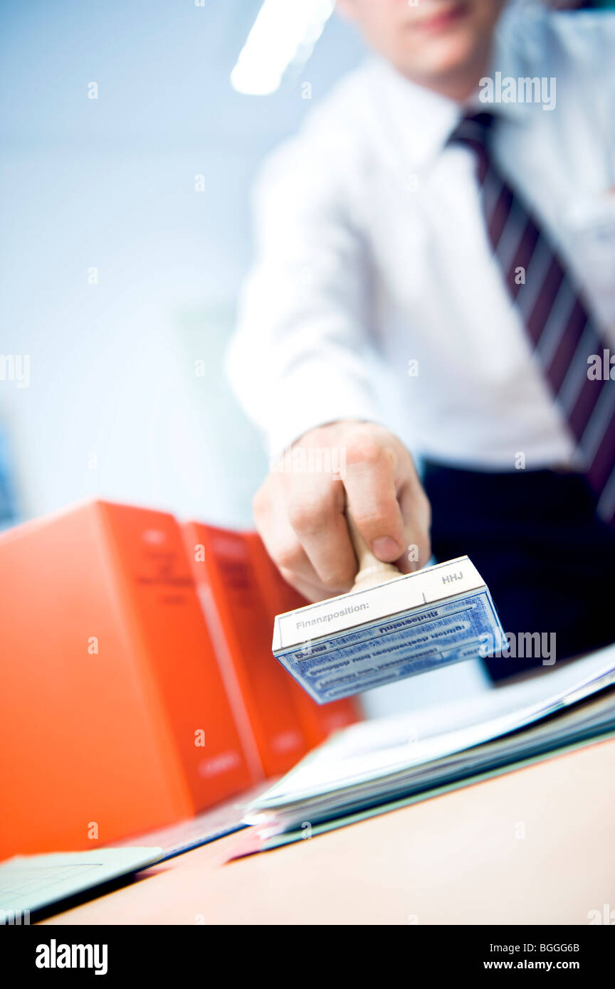 Man holding a stamp above a stack of papers, slanted view - Stock Image