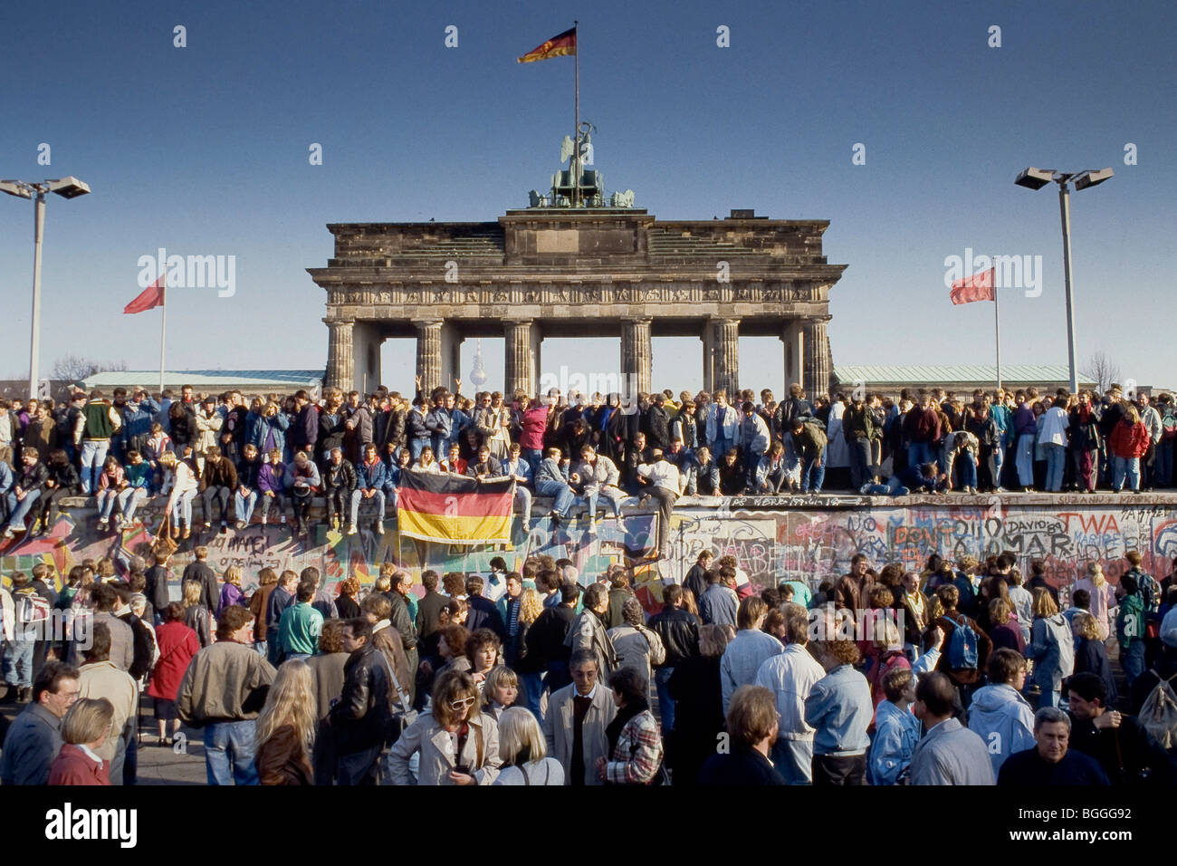 Fall of the Berlin Wall: people from East and West Berlin climbing on the Wall at the Brandenburg Gate, Berlin, Stock Photo