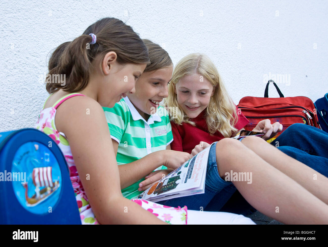 Three girls reading a magazin - Stock Image