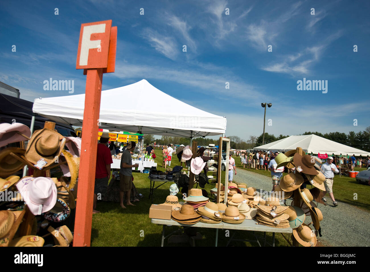 A hat vendor sells their wares outside row orange F at the Foxfield Races, Charlottesville, Virginia, USA. - Stock Image