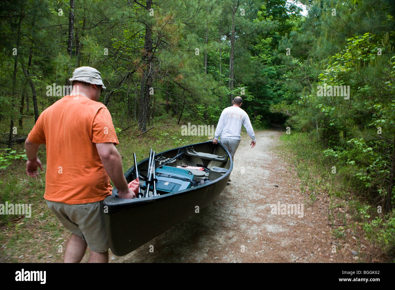Two men portaging a canoe down a trail, Congaree National Park, near Columbia, South Carolina. - Stock Image