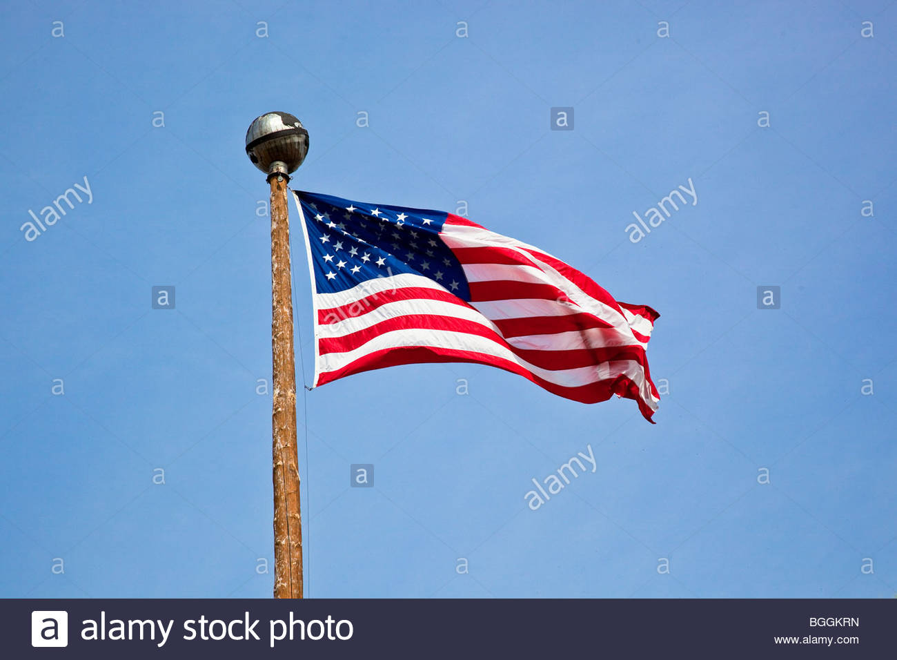 Brilliant American flag flying atop the pole on the Delaney Park Strip in Anchorage, Alaska on July 4, 2009 against - Stock Image