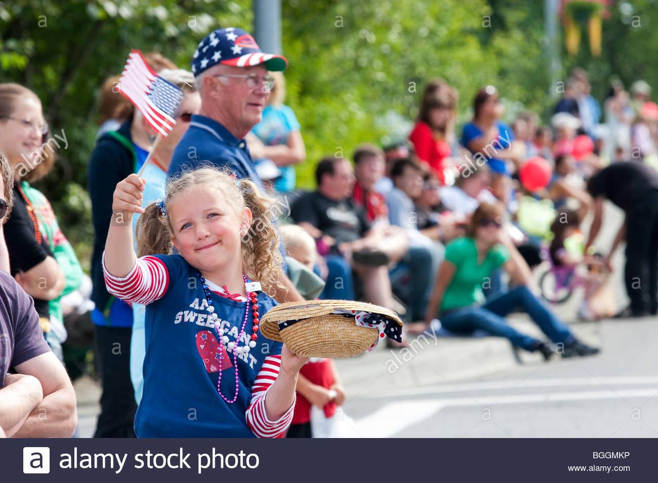 Alaska, Wasilla Girl waves flag at Independence Day parade in Wasilla. - Stock Image