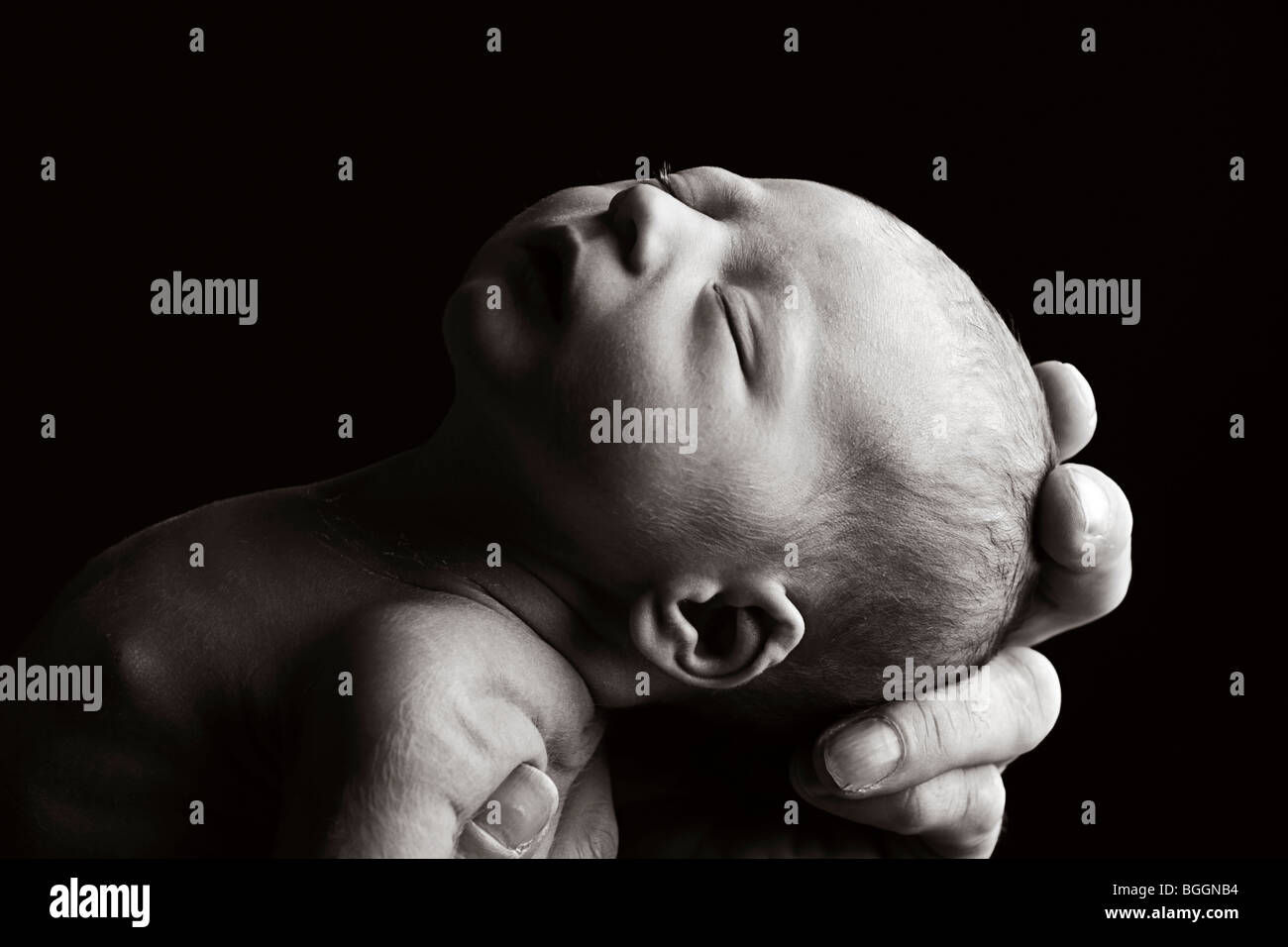Beautiful Low Key Shot of a Father's Hand Holding a New Born Child - Stock Image