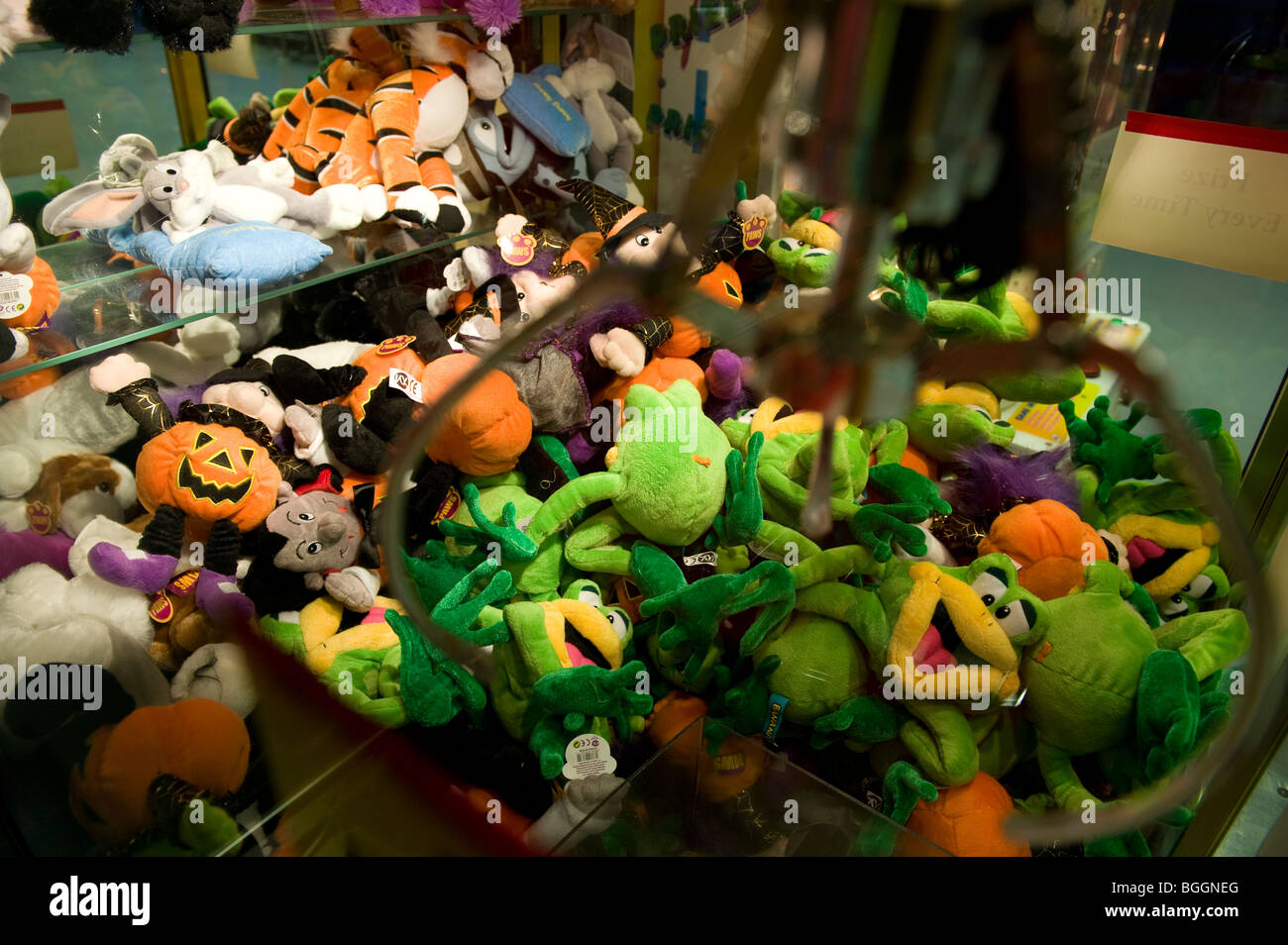 Soft toys as prizes in a grabber machine, where toys can be won for money. - Stock Image
