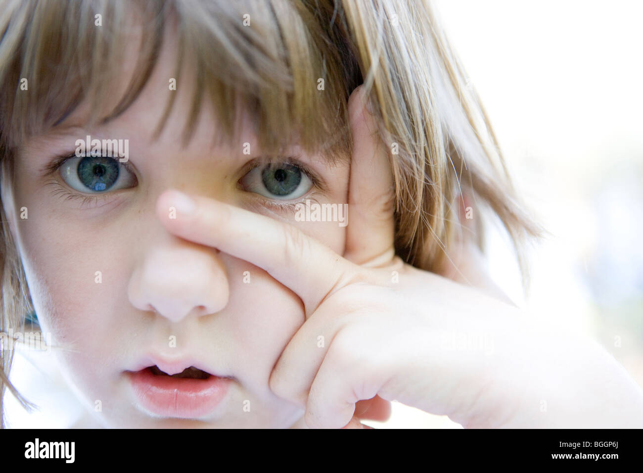 eight year old child looking at camera with fingers on her face - Stock Image