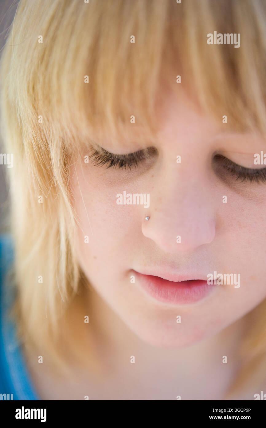 teenage girl depressed, looking down, closeup of face - Stock Image