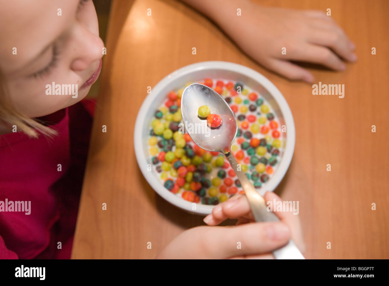 ten year old girl eating sugar cereal at home, high angle view - Stock Image