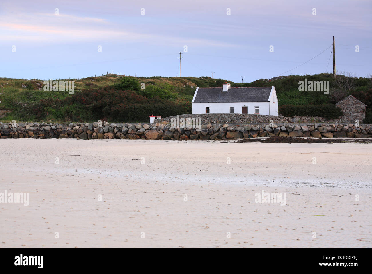 traditional Irish cottage at the beach in Carna near Roundstone and Galway in Connemara, Ireland - Stock Image