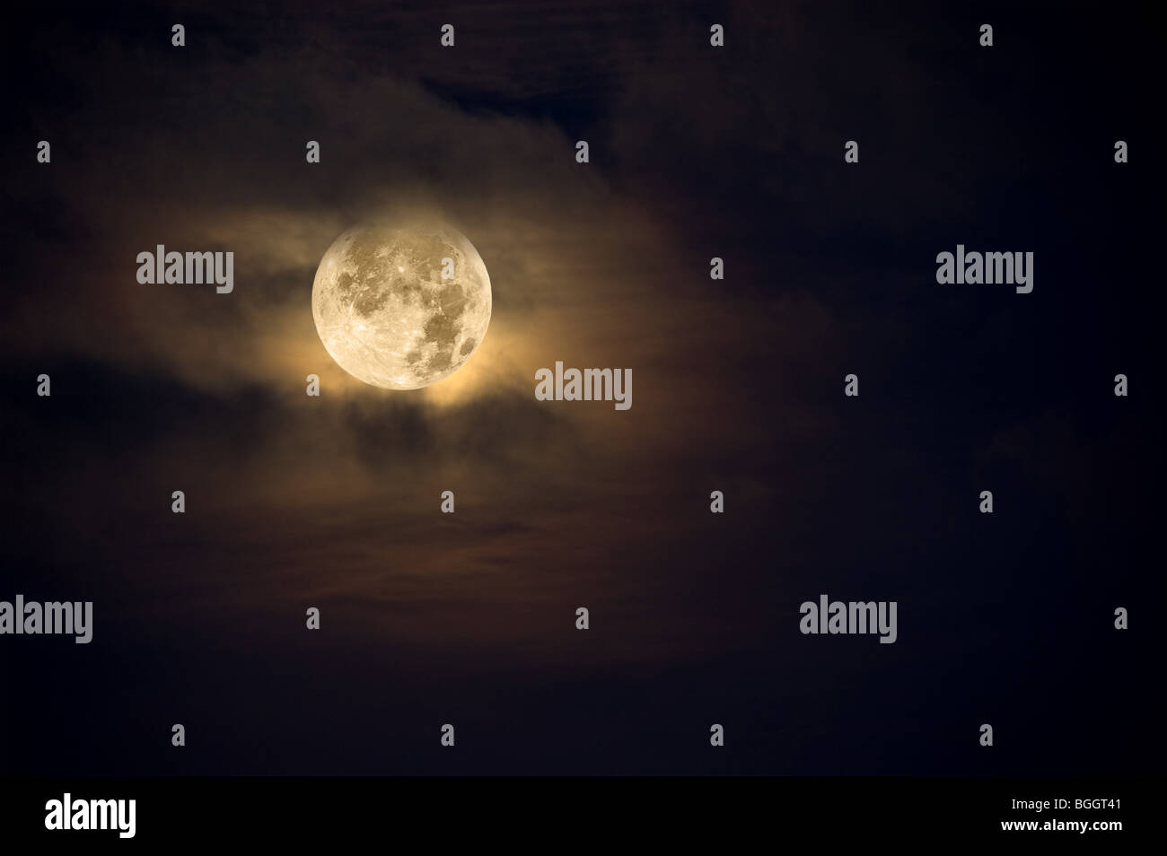 A dark night brings a bright, amber moon alive with puffy hazy clouds. - Stock Image