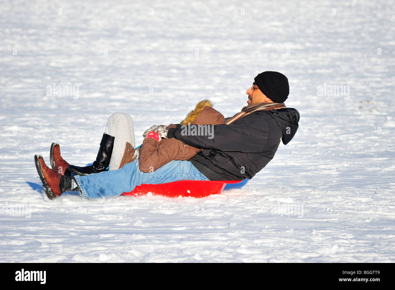 Farther and child on sledge - Stock Image