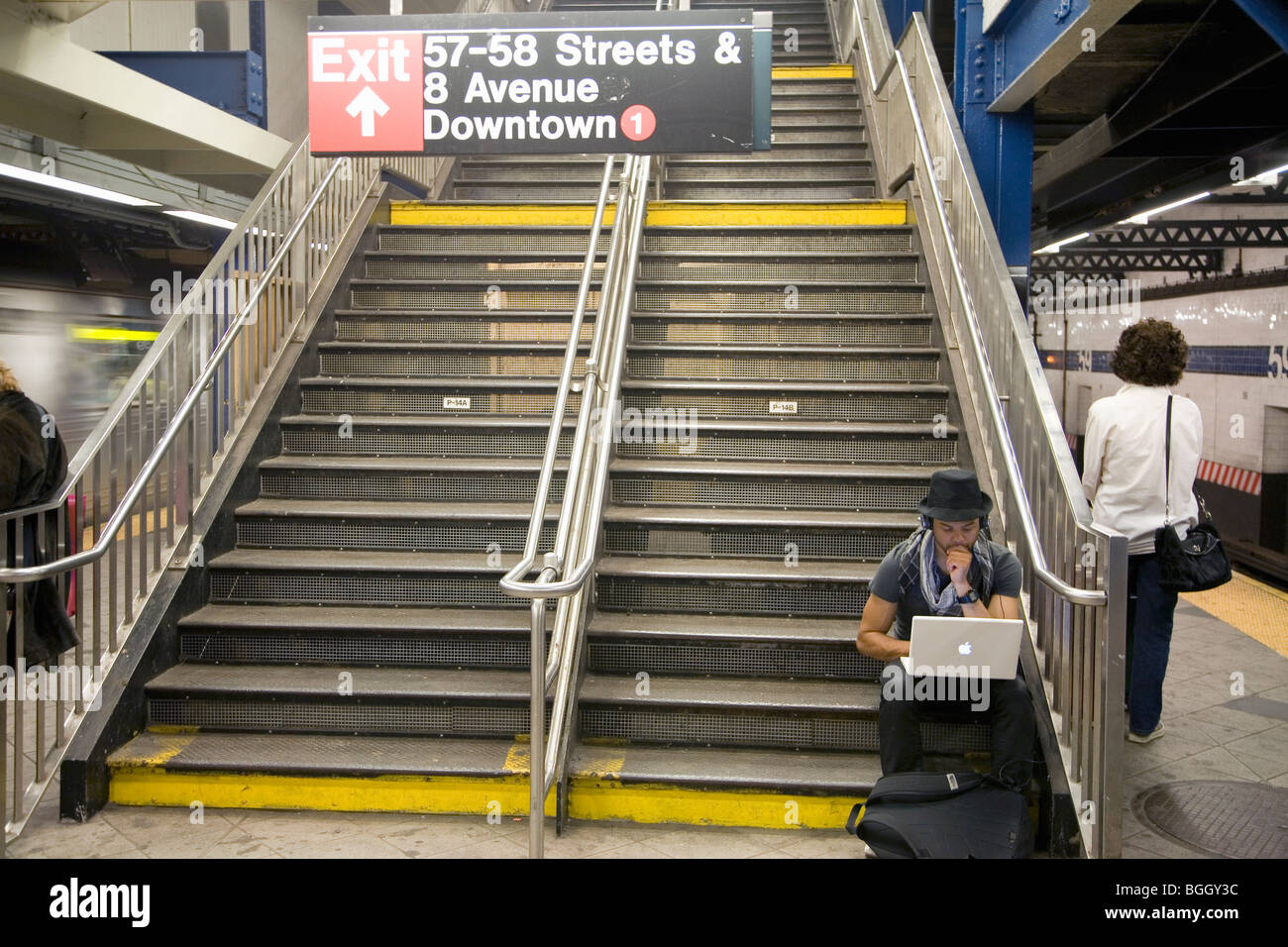 Apple laptop computer user sits on stairwell of New York City subway system - Stock Image