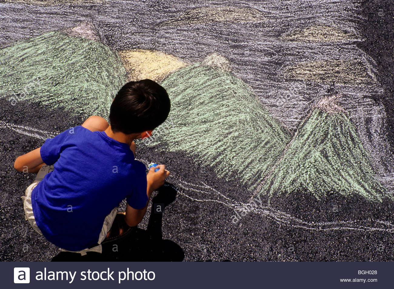 Alaska. A boy is creative with chalk drawing his vision of Alaska on a summer day. - Stock Image