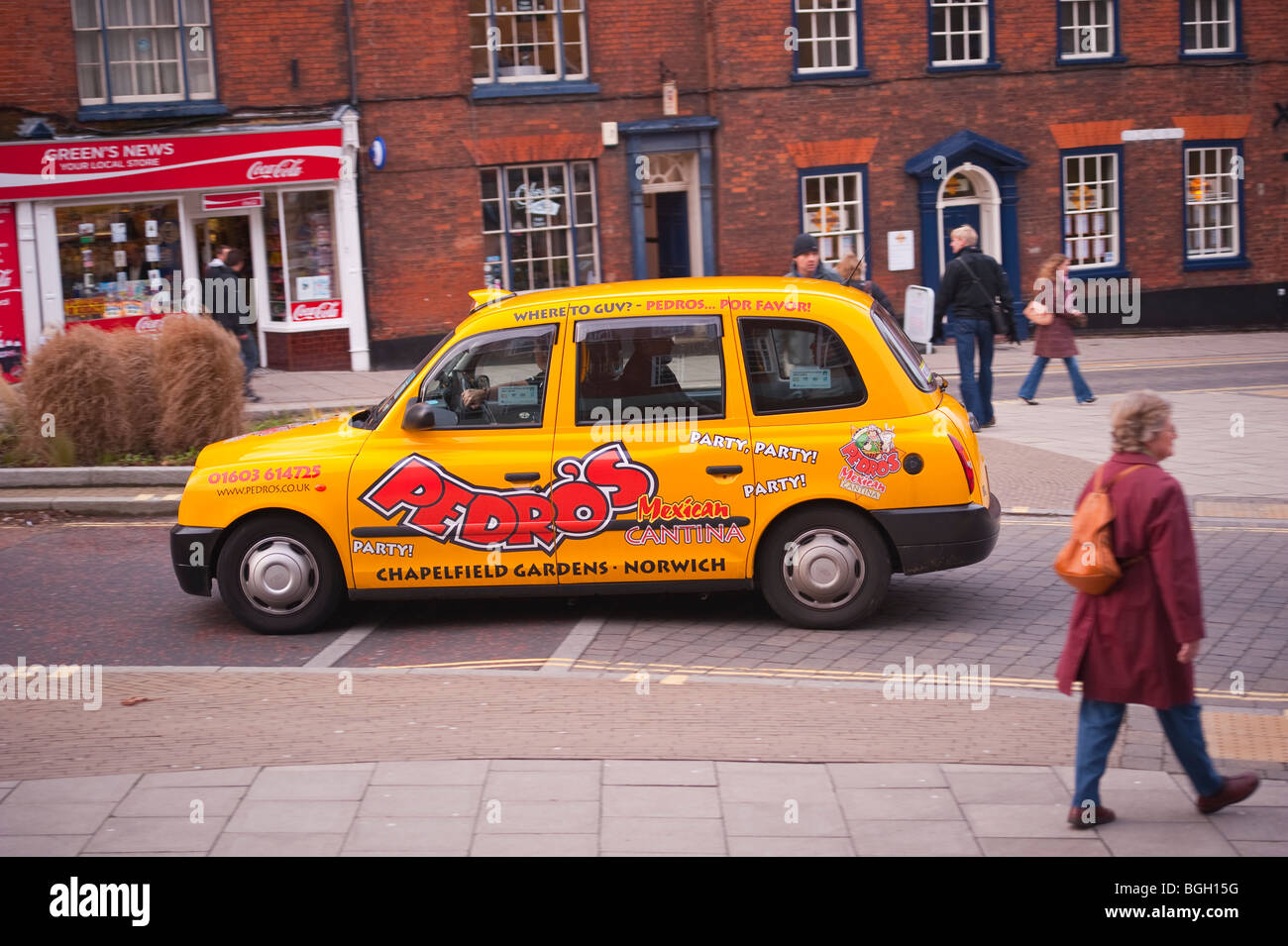 A yellow taxi cab drives through the city showing movement in Norwich,Norfolk,Uk - Stock Image