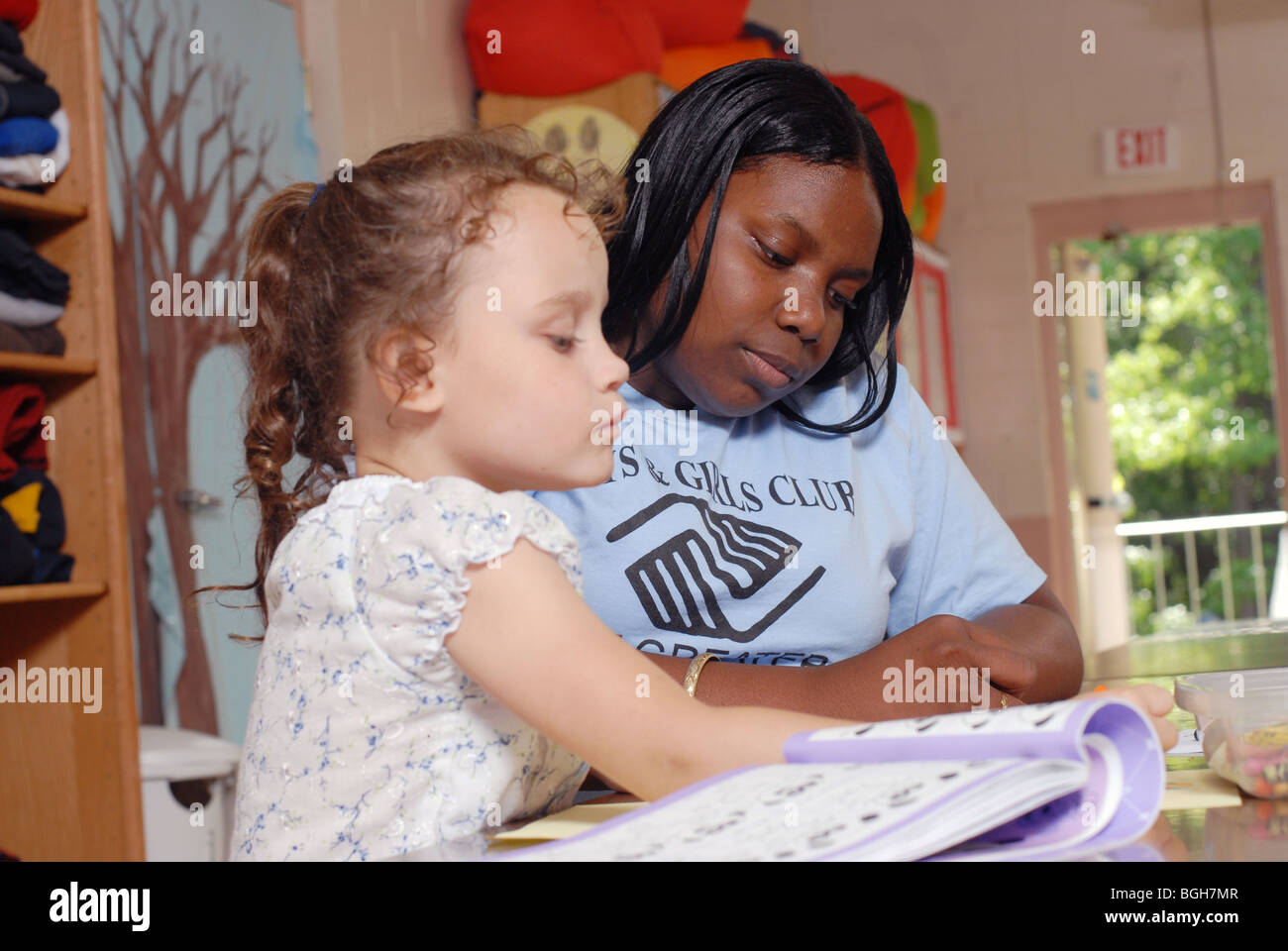 African american camp counselor works with twin girls at boys and girls club of nashua nh image is model released