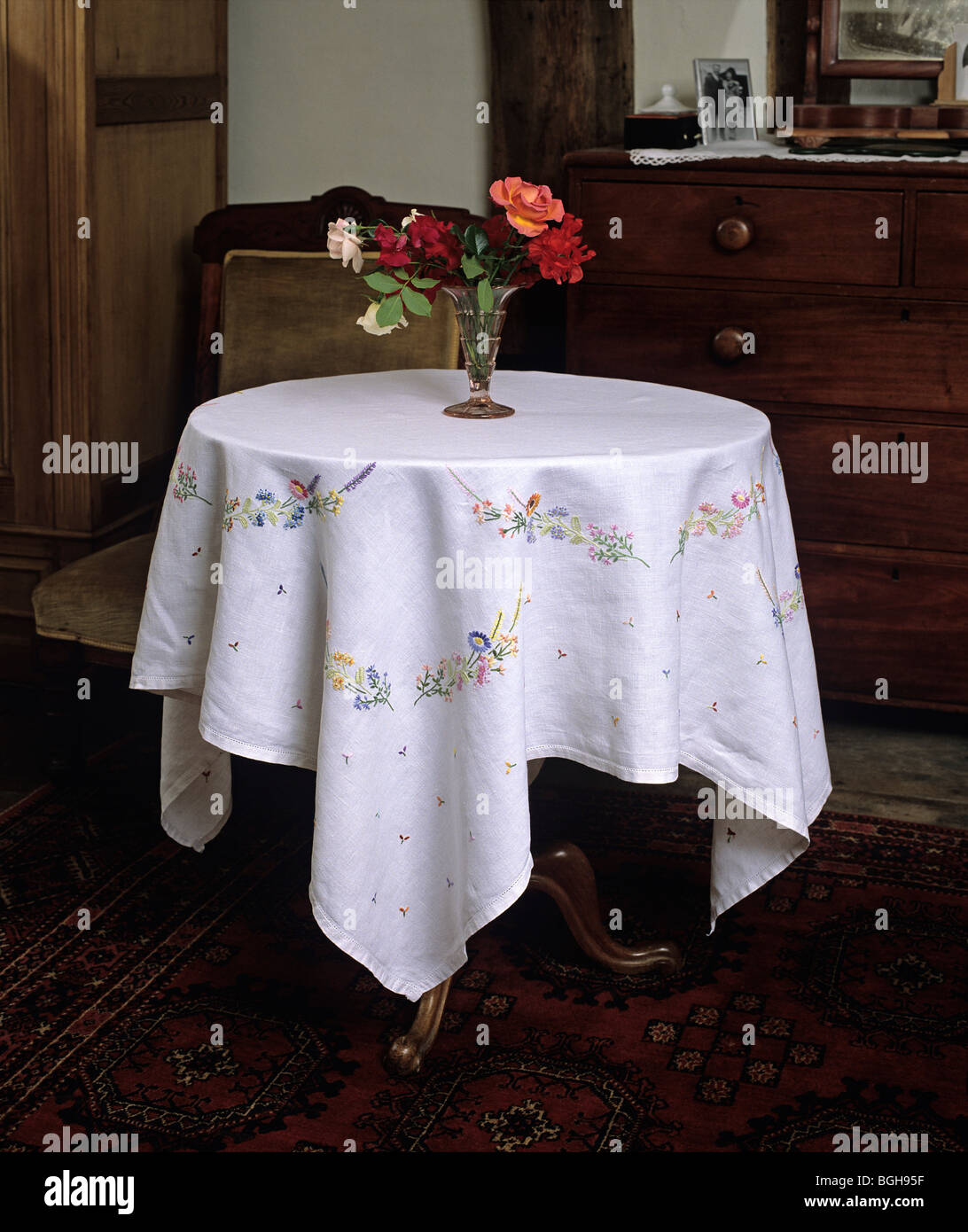 Small Round Table With Embroidered Victorian Tablecloth Stock