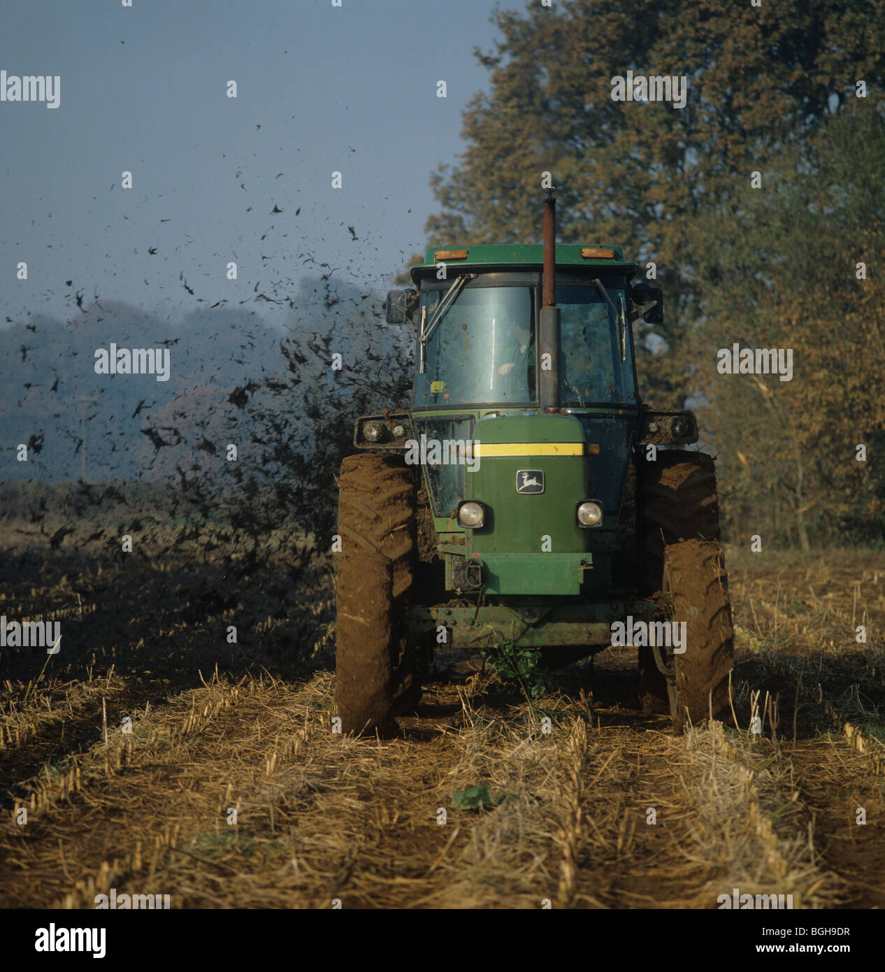 John Deere tractor spreading muck onto maize stubble before cultivation and replanting - Stock Image