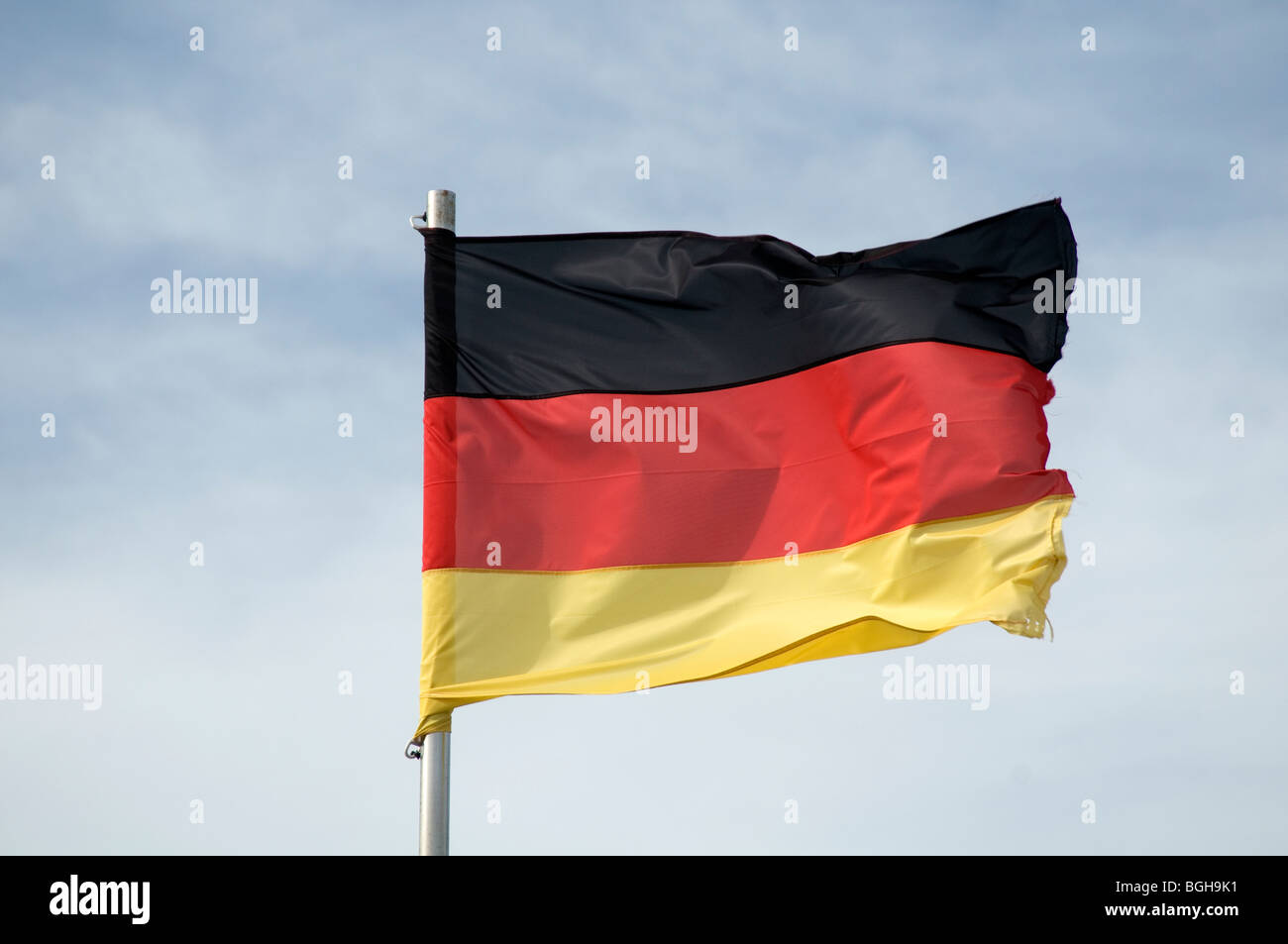 german flag germany flags tricolor deutschland deutsch pole flagpole national pride bluesky sky skies blue - Stock Image