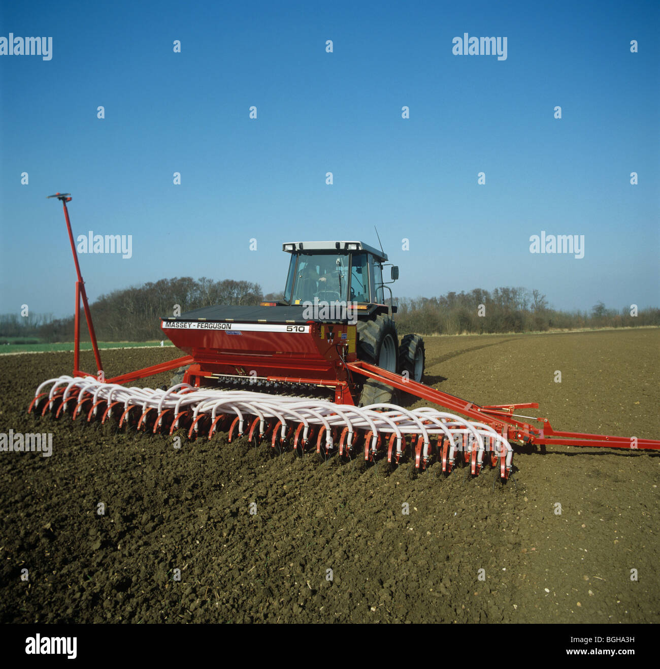 Massey Ferguson pneumatic seed drill planting a cereal crop in early spring - Stock Image