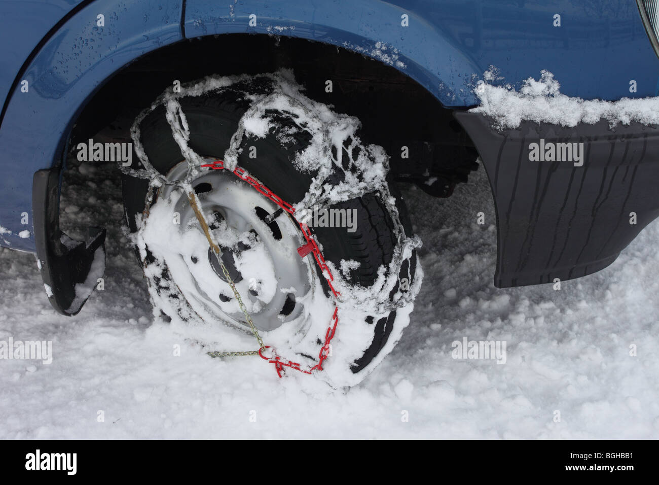 Side View of Snow Chains Fitted to a Vehicle in Winter - Stock Image