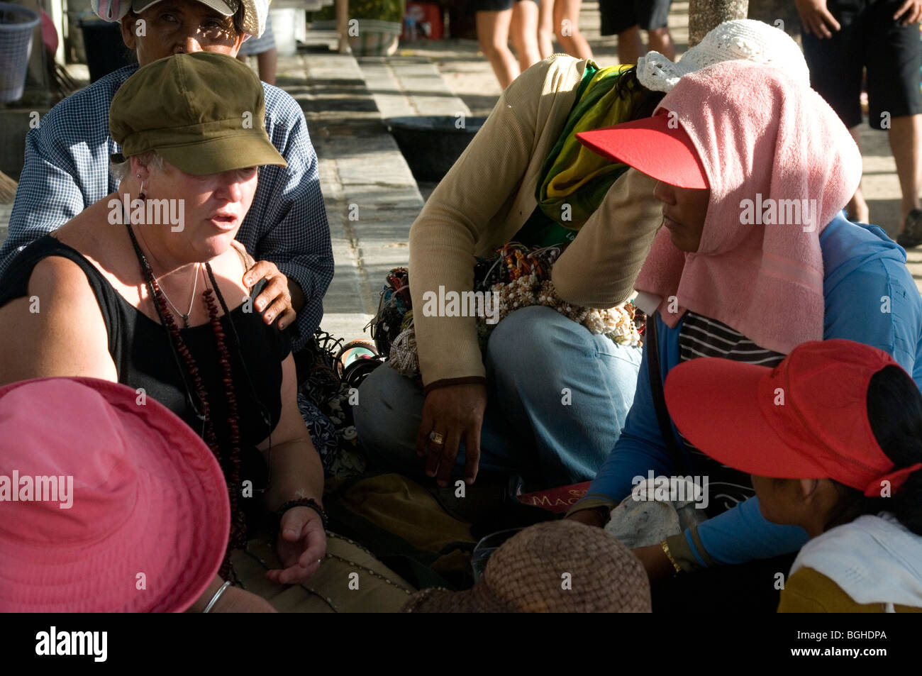 Woman tourist targetted by hawkers and masseurs, Kuta Beach, Bali, Indonesia Stock Photo