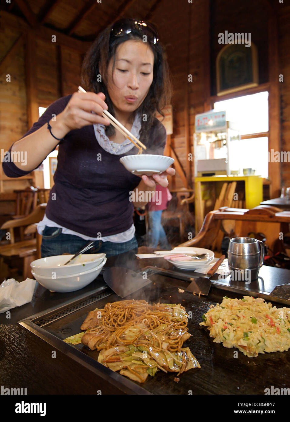 Okonomi yaki. Japanese style savoury pancakes being cooked on a hot plate. Japan - Stock Image