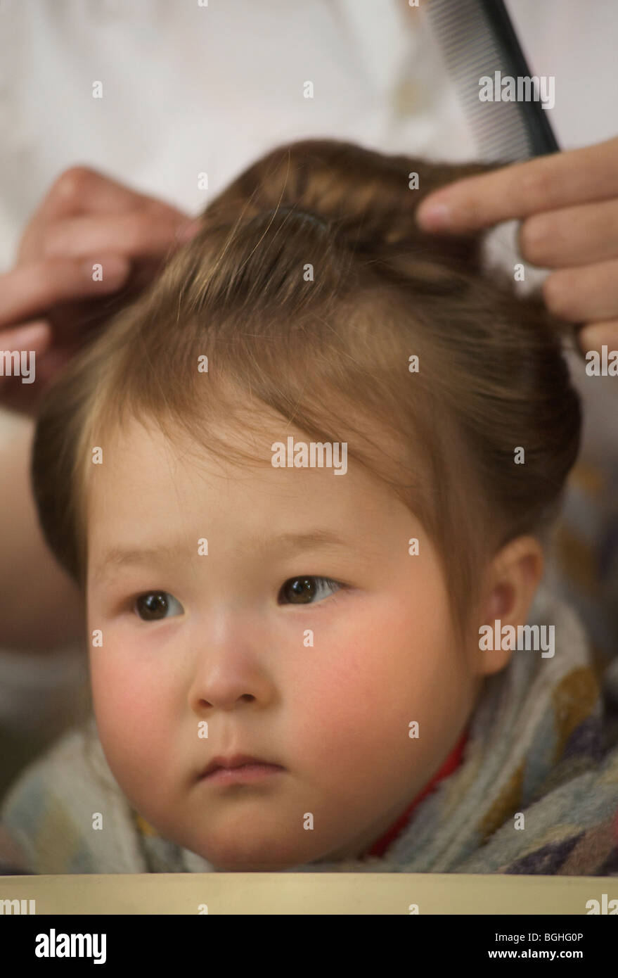 Two year old girl having her hair styled. - Stock Image