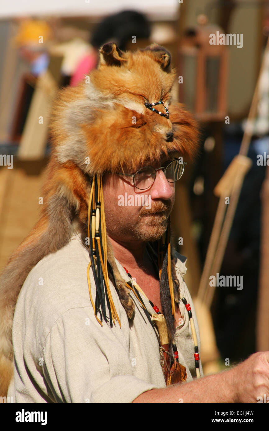 Mountain Man with Red Fox Animal Hat Throws Knife or Hatchet
