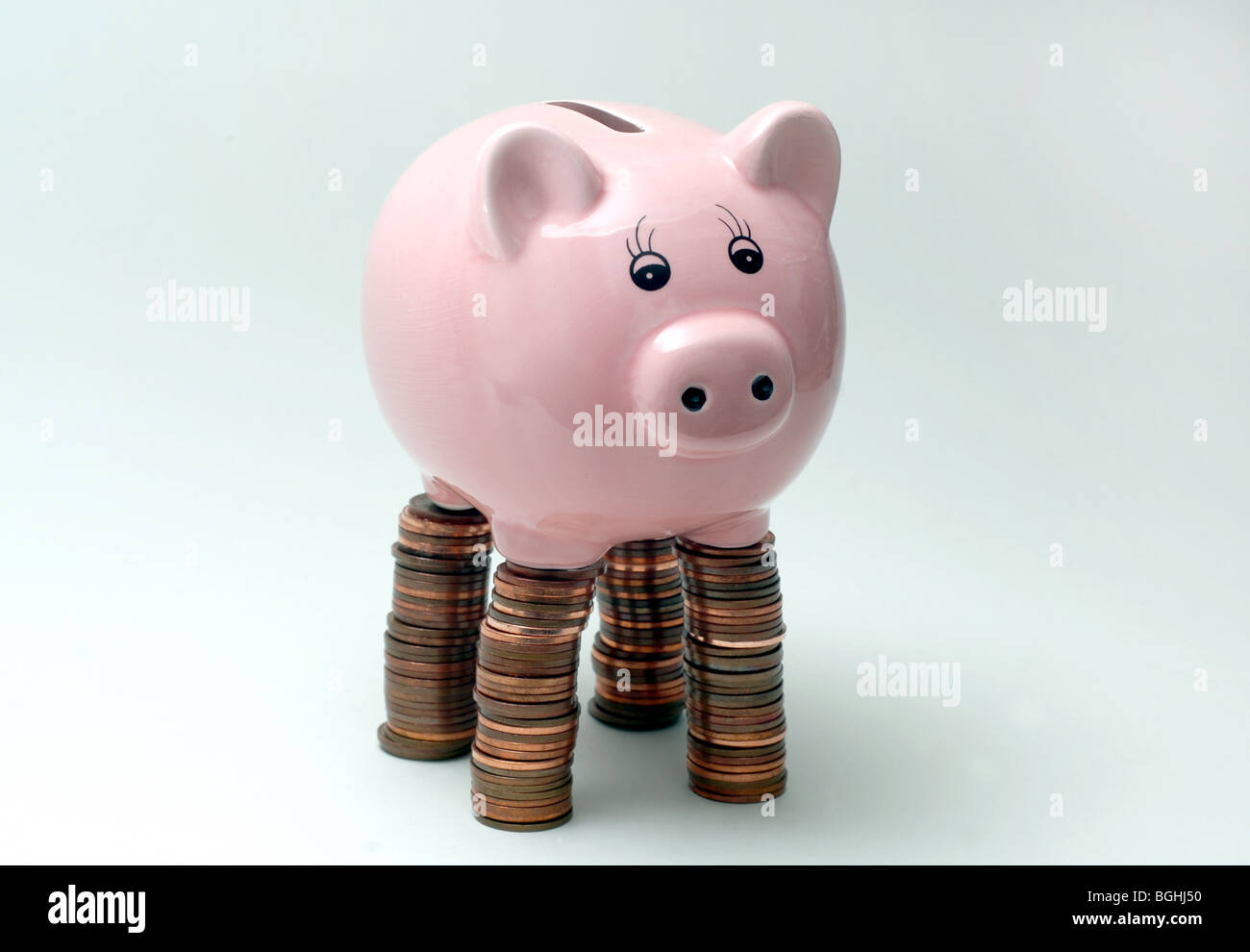 PIGGY BANK,PIGGYBANKS STANDING ON PILES OF BRITISH COINS RE THE ECONOMY SAVINGS INCOMES MORTGAGES  THE ECONOMY UK - Stock Image