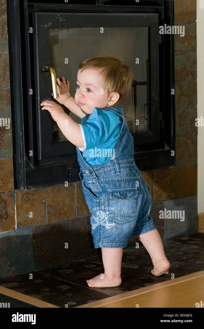 one year old baby playing close to the fire place - Stock Image