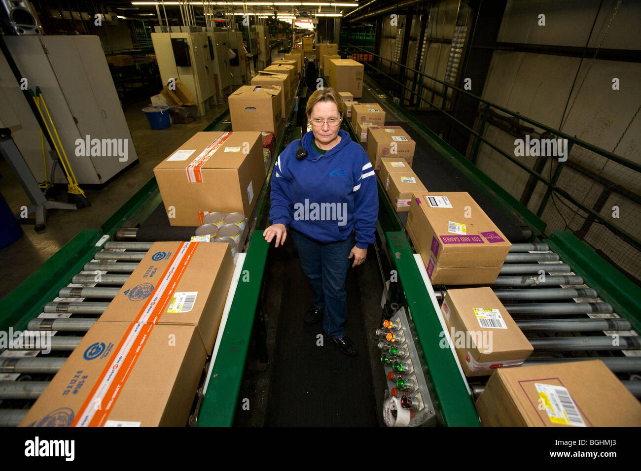 A Walmart Stores Inc. associate keeps watch over a conveyor line at a Distribution Center in Arkansas. - Stock Image