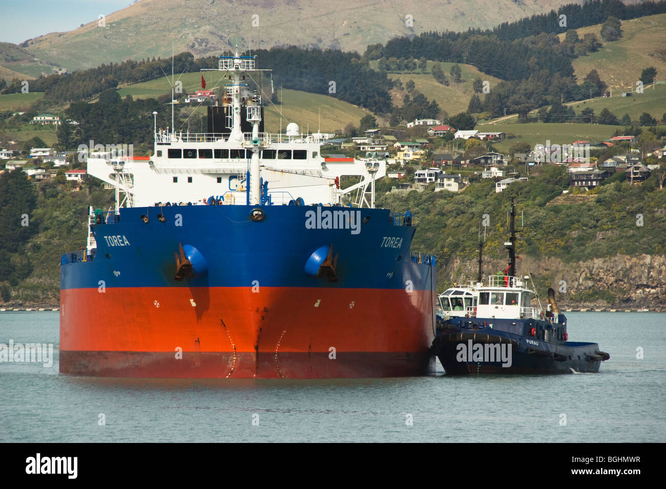 A tanker is assisted into port by  tugs. - Stock Image