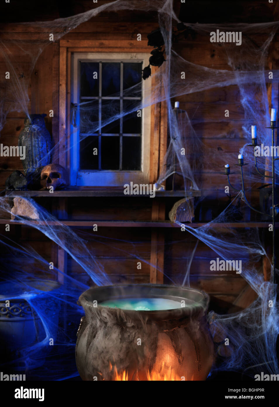 Steaming potion in a cauldron inside a witch cabin - Stock Image