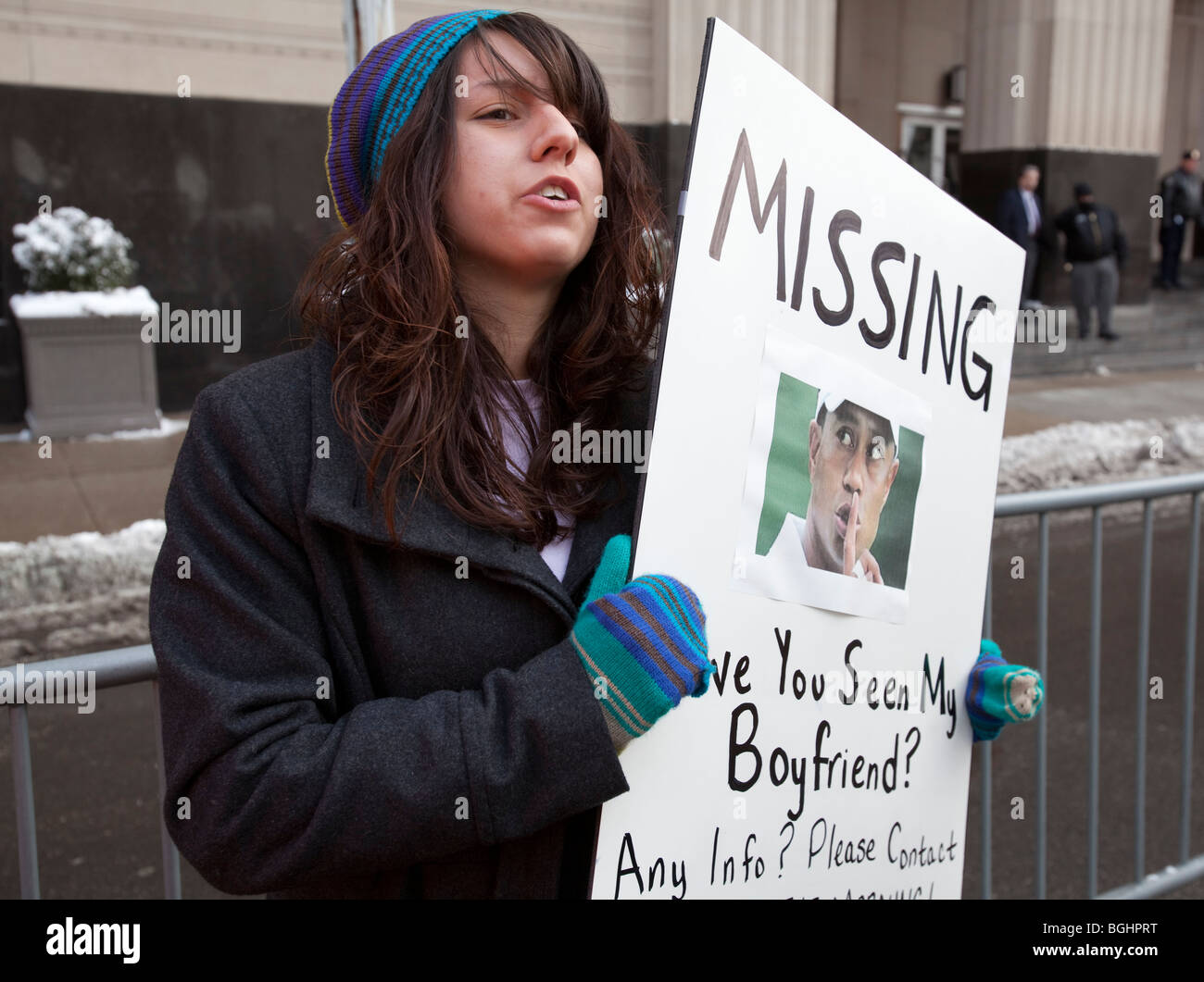 A girl holds a poster claiming that Tiger Woods is her missing boyfriend. - Stock Image