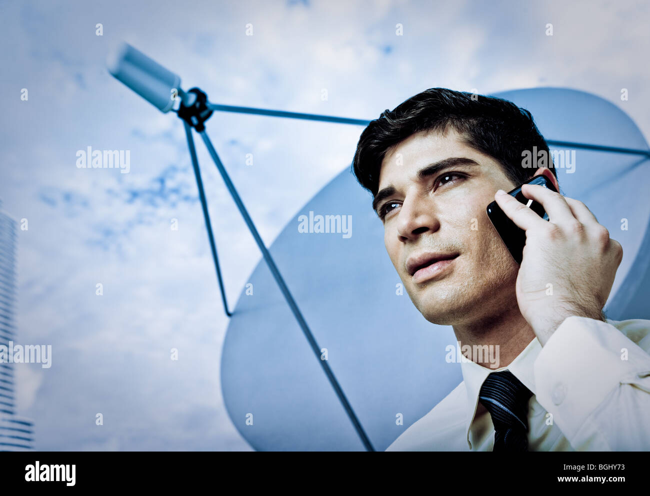 A young male businessperson on a cellular phone with satellite dish in background. - Stock Image