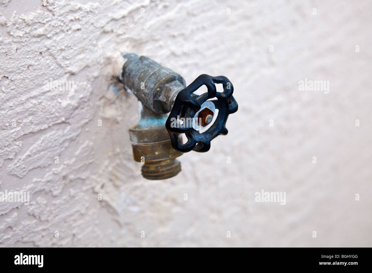 water spigot with backflow preventer valve on stucco wall - Stock Image