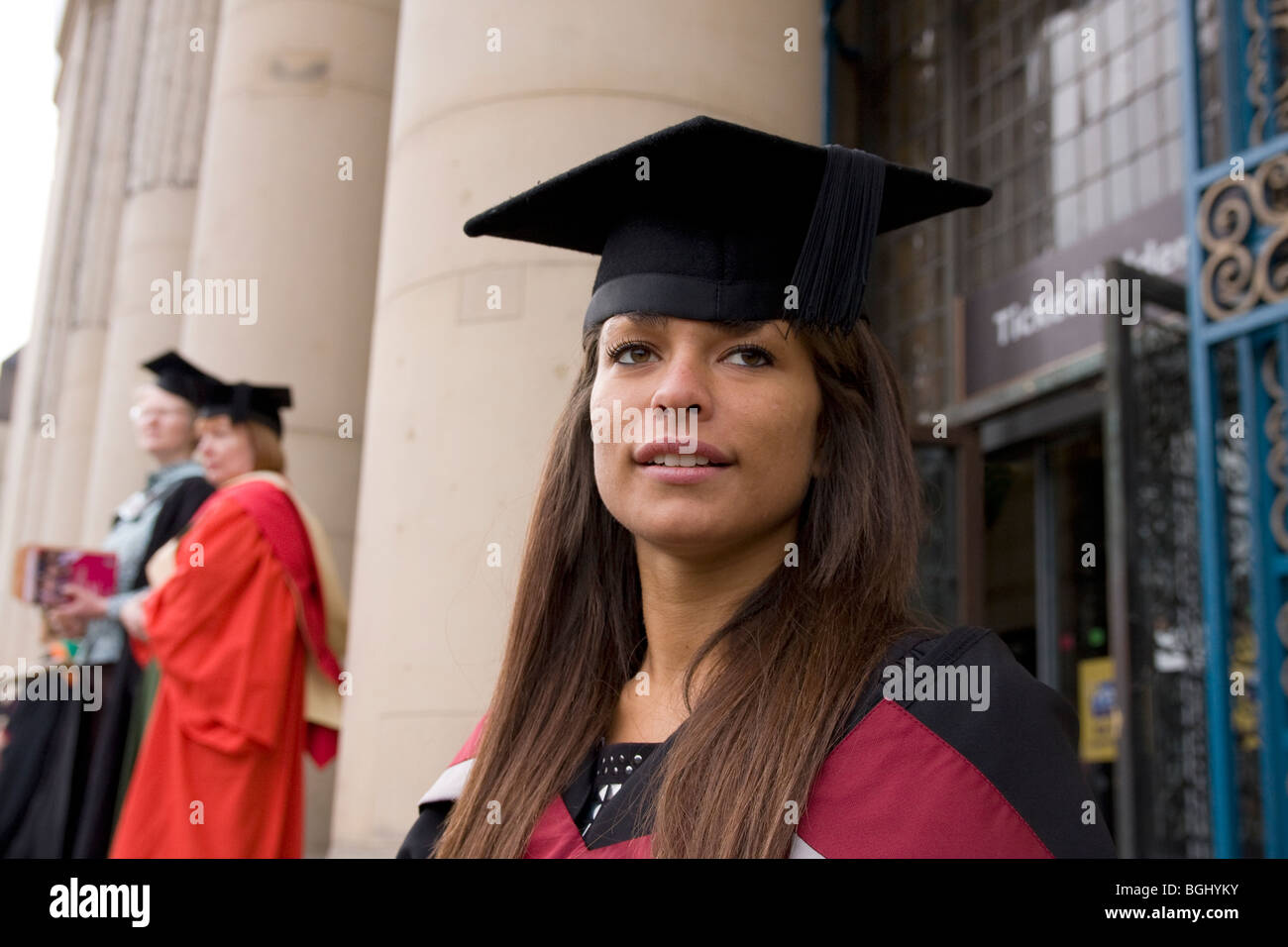 apprehensive young woman on graduation day outside venue - Stock Image