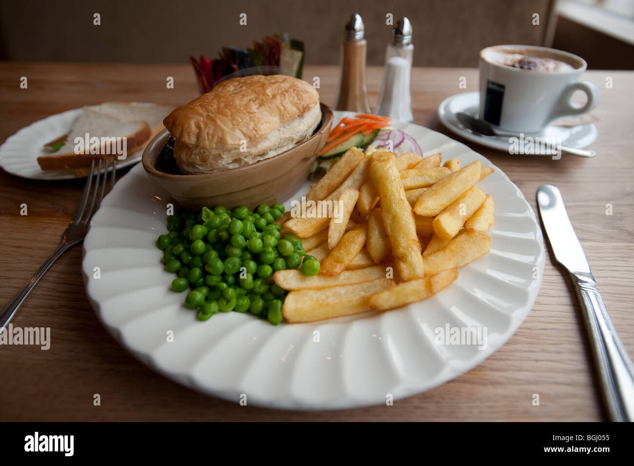 steak and kidney meat pie chips and peas on plate in cafe UK - Stock Image