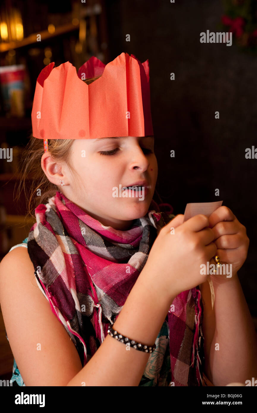 child wearing a paper party hat reading a joke from a christmas cracker - Stock Image