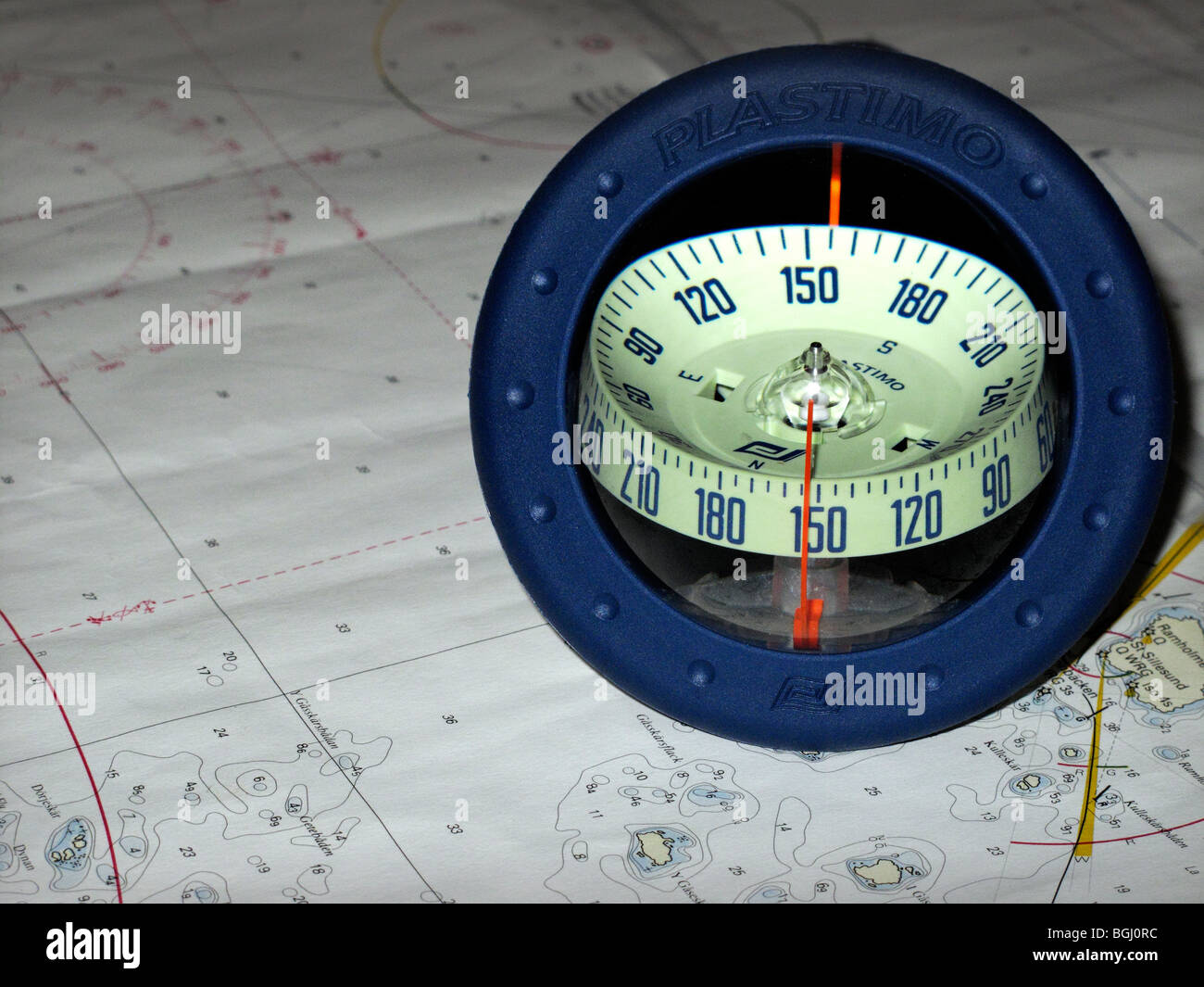 Spherical sailing dinghy compass on surface of nautical chart. - Stock Image
