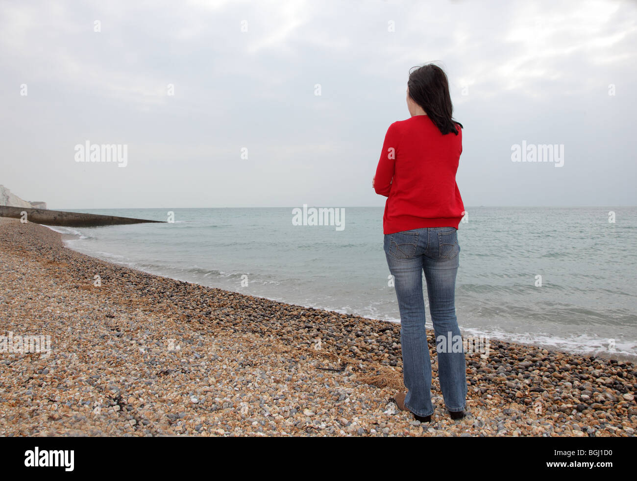 Woman standing on a beach wearing jeans and a red top, back view - Stock Image