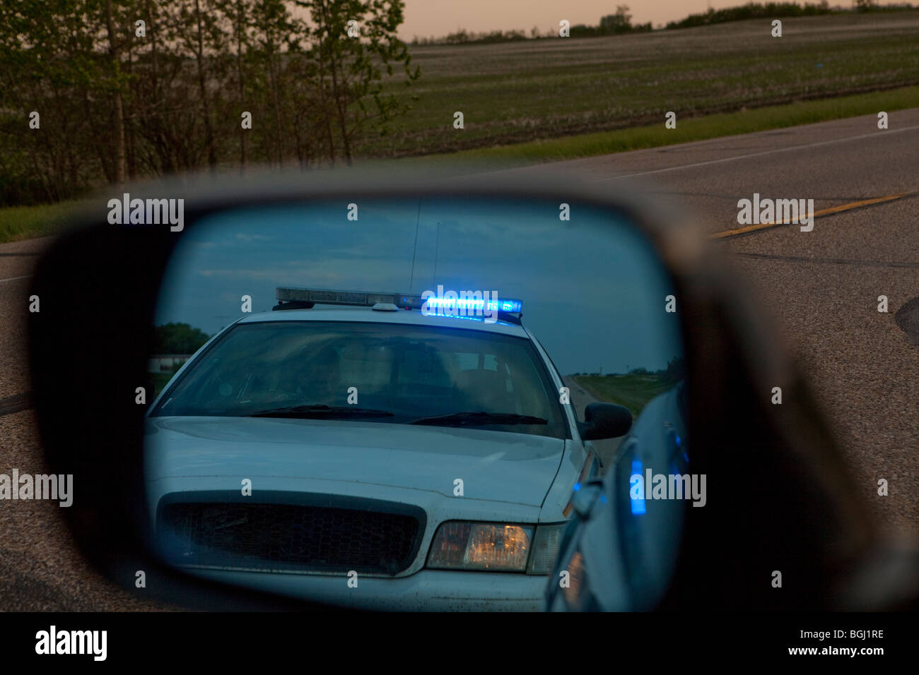 A Police Car In The Rear View Mirror Of A Vehicle   Stock Image