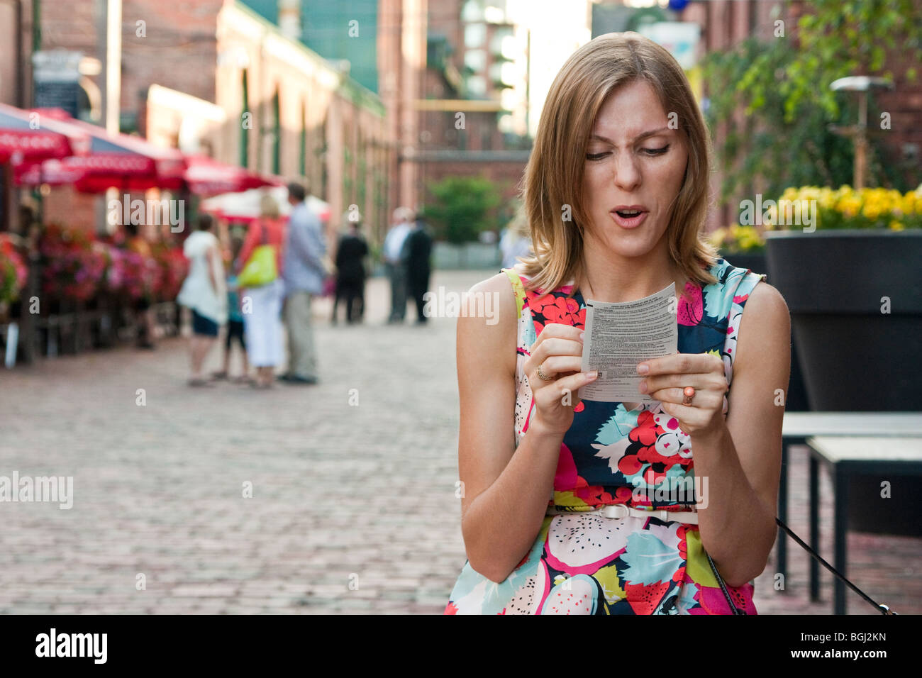 Young woman playing a scratch-off lottery, unhappy with the results - Stock Image